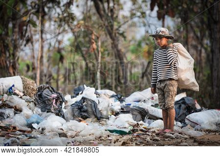 Poor Boy Collecting Garbage In His Sack To Earn His Livelihood, The Concept Of Poor Children And Pov
