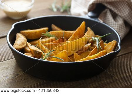 Roasted Potato In A Frying Skillet Pan On Wooden Table. Homemade Roasted Potatoes Slices.