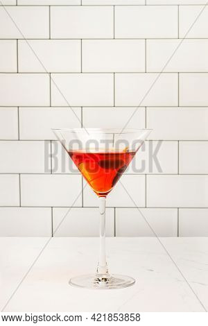 A Glass Of Red Vermouth On A Marble Countertop And In Front Of A Subway Tiles Wall