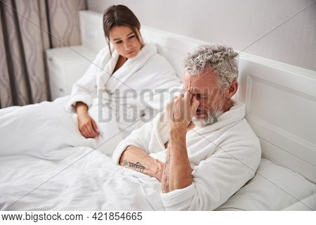 Thoughtful Bearded Man Sitting On The Bed With His Wife In Home Apartment