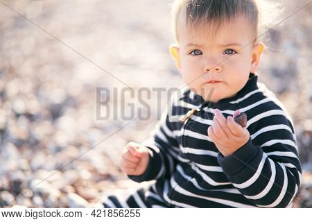 Serious Baby In A Striped Overalls Sits On A Pebble Beach, Holding A Pebble In His Hand. Close-up