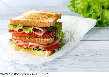 Tasty Sandwich With Ham, Salad And Tomatoes On Light Background