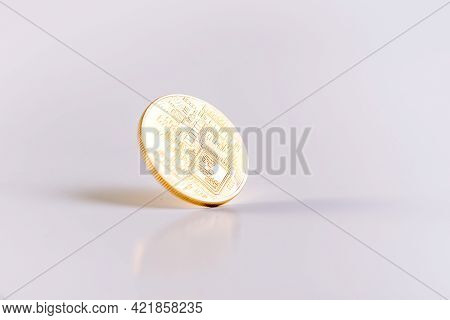 Reverse Of A Bitcoin Coin Spinning On A White Table. Copy Space. White Background. Isolated. Falling