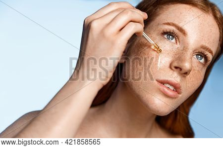 Woman Applying Hyaluronic Serum On Her Face With Pipette. Photo Of Attractive Woman With Perfect Mak