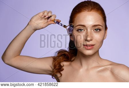Redhead Beauty Girl Massages Skin With Face Roller, Smiling Pleased At Camera. Woman Self-massage Wi