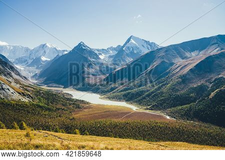 Wonderful Alpine Landscape With Mountain Lake And Mountain River In Valley With Forest In Autumn Col