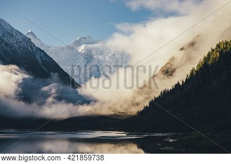 Wonderful View Of Snow-capped Mountains Above Thick Clouds In Gold Sunshine. Scenic Landscape With A