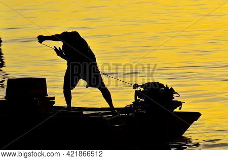Silhouette Of A Fishermen On Boat With Outboard Motor Boat Ready To Fishing During Beautiful Sunrise
