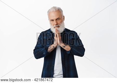 Please. Serious Senior Man With Tattoos Asking For Favour, Begging Help, Holding Hands In Namaste Pl