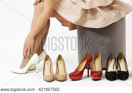 Woman Sitting Trying On High Heeled Shoes On White Background