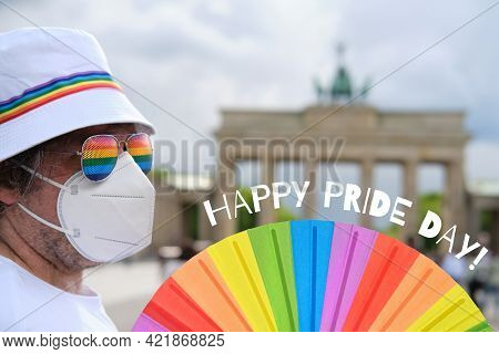Mature Caucasian Lgbt Man In Berlin With Rainbow Fan And Ribbon On White Summer Hat. Rainbow, Symbol