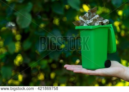 Female Hand Is Holding Green Plastic Recycle Garbage Bin At Park. Waste Recycling Sorting Management