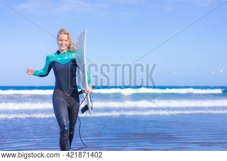 Young Sexy Girl With Long Blonde Hairs, Smiling And Jogging With Surf Board On The Beach In A Summer