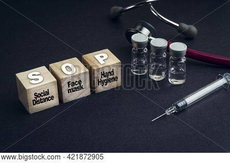 Sop Text Or Standard Operating Procedure On Wooden Cube With Stethescope And Syringe On Black Backgr
