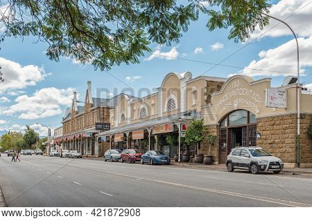 Oudtshoorn, South Africa - April 5, 2021: A Street Scene, With Businesses, People And Vehicles, In O