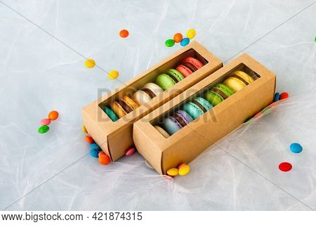 Multicolored Macarons In A Paper Box And Multicolored Sweets On A Romantic Background.
