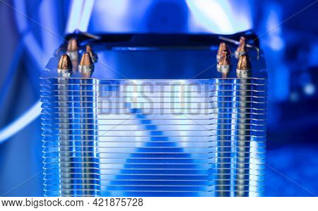 Cooling. Aluminum fin radiator of LED illuminated CPU cooler, light coming through the radiator fins. Focus on fin edges.  Cooling fan for PC equipment. Extremely Shallow depth of field.
