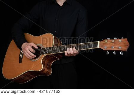 A Man's Hand While Playing An Electro-acoustic Guitar. Blow It Up. A Human Hand Plays The Guitar. Sc
