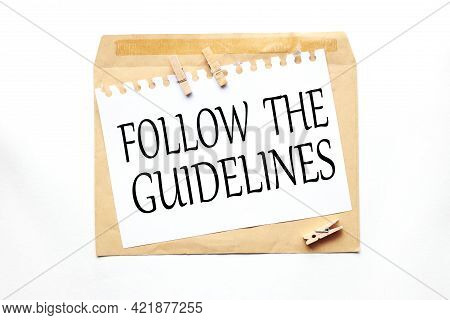 Follow The Guidelines. Text On White Paper On Craft Notebook