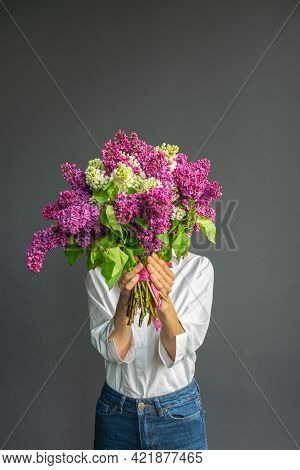 A Faceless Caucasian Woman Holding A Bouquet Of Flowers In Her Hands On A Dark Background. Spring Co