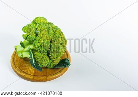 Large Raw Fresh Head Of Broccoli Cabbage On A Wooden Board, White Background, Healthy Vegetarian Foo