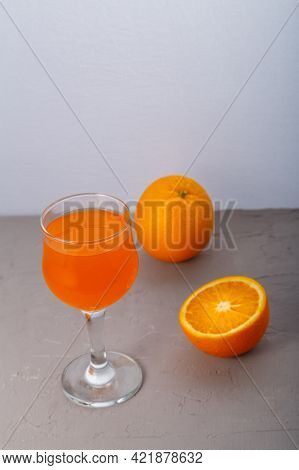 Orange Juice In A Glass Near Oranges On A Gray Background Vertical Photo.