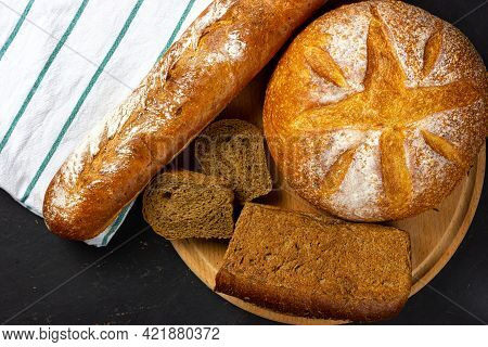 Lots Of Fresh Bread On The Black Table. A Loaf Of Rural Bread. Round Bread. Rye Bread