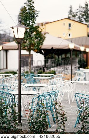 Open-air Restaurant. Wicker Chairs And Tables Stand Outside Near Glowing Lanterns Against The Backdr