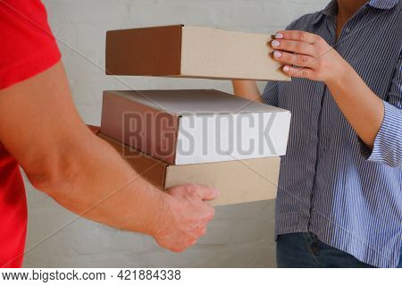 A Delivery Courier In A Red Uniform Hands Over Cardboard Boxes To A Woman Against The Backdrop Of A