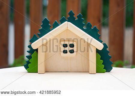Small Wooden Handmade Dollhouse With Green Spruce On The Back. Handcrafted Wood Waldorf Toy For Kids
