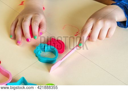 Girl Toddler Holds Pink Play Clay By One Hand And Toy Tool By Other Hand. Play Dough Mold In Shape O