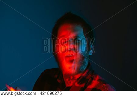 Conceptual Portrait, With Movement And Out Of Focus Of A Tattooed Person Screaming With A Gesture Of