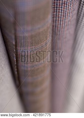Online Sale Or Tailoring Objects Concept. Closeup Bunch Of Warm Wooled Tweed Textile Rolls In Differ