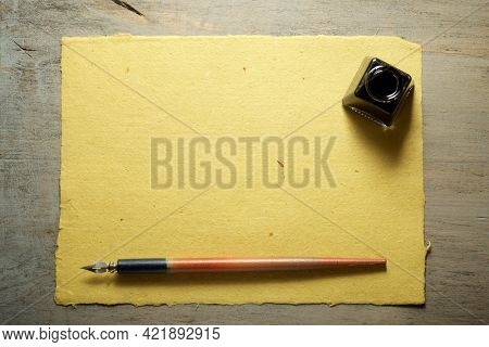Nib pen for calligraphy and inkwell on a yellow handmade craft paper.