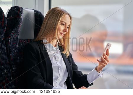 Subway commuter business woman on public transport using smartphone