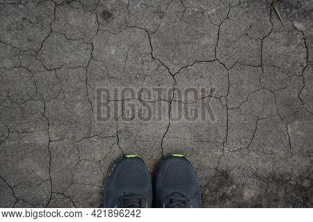 On Arid Ground, Cracked Everywhere At The Bottom Of The Frame, Two Sneakers Peek Out. There Is Plent