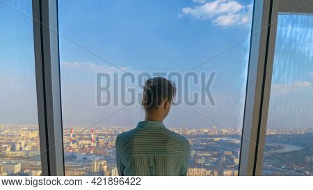 Back View Of Pensive Woman Looking At Cityscape And Blue Sky Through Window Of Skyscraper. Summer Ti