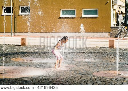 Summer Heat.the Girl Splashes In The Fountain On A Summer Day.little Cute Girl Walking In Open Stree