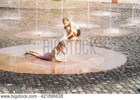 Two Little Girls Sisters Splashing In The Fountain On A Summer Day. Summer Heat.little Cute Girl Wal