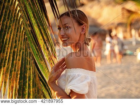 Cheerful Young Woman Enjoying A Day On The Sea Shore At Sunset.