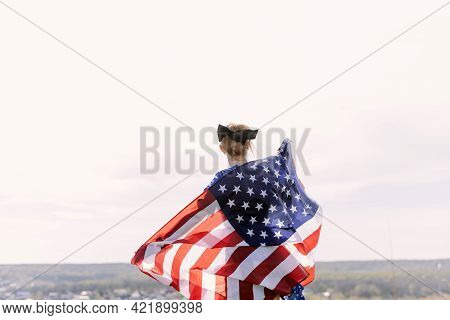 Young Beautiful Woman Holding Usa Flag. The Back Of A Young Woman With The Us National Flag On Her S