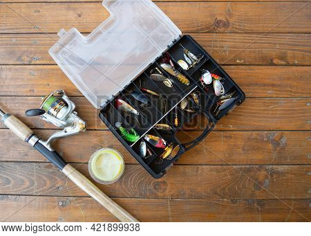 Background Fishing Gear And Fishing Rods. Fishing Rod, Spinning Rod And Various Baits On A Wooden Ta