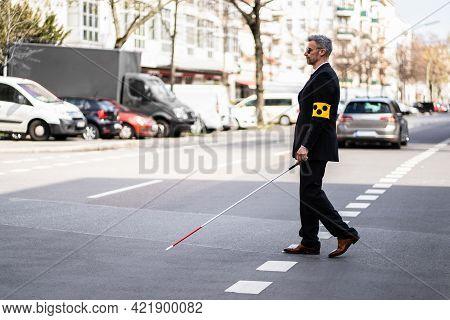 Blind Man Walking On Sidewalk Holding Stick Wearing Armband