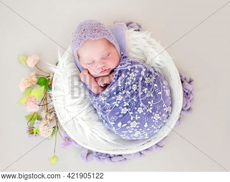 Newborn baby girl swaddled in beautiful fabric and wearing knitted hat sleeping in white basin. Little cute infant child napping lying on white fur. Adorable kid during studio photoshoot