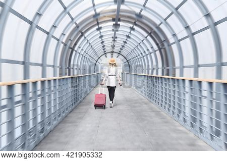 Woman Traveler With A Suitcase Goes Into The Distance Along The Gallery Of The Covered Passage