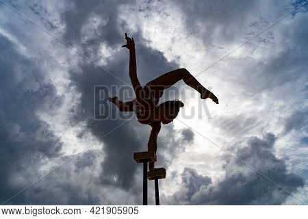 Flexible Female Circus Artist Keep Balance On Hands Against Amazing Cloudscape. Individuality, Outst