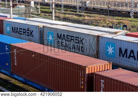 Close-up Freight Train With Cargo Containers Maersk And Other Carriers. International Container Carg