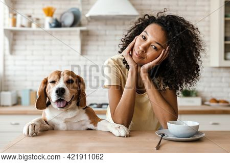 Smiling young african woman leaning on a kitchen counter with her pet beagle