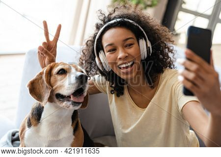Happy young african woman in headphones relaxing on a couch with her pet dog at home, taing a selfie