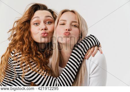 Young two women hugging and making kiss lips together isolated over white background
